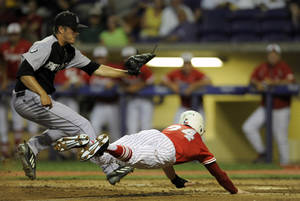 Photo - Houston's Kyle Survance (34) beats a tag at home plate by Bryant pitcher Kevin Mcavoy (31) during an NCAA college baseball tournament regional game in Baton Rouge, La., Friday, May 30, 2014. (AP Photo/Stacy Revere)