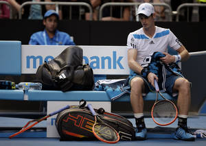 Photo - Andy Murray of Britain sits in a chair beside his smashed racket during a break in his fourth round match against Stephane Robert of France at the Australian Open tennis championship in Melbourne, Australia, Monday, Jan. 20, 2014.(AP Photo/Rick Rycroft)
