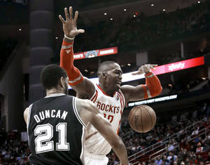 Photo - San Antonio Spurs' Tim Duncan (21) knocks the ball away from Houston Rockets' Dwight Howard (12) during the first half of an NBA basketball game Tuesday, Jan. 28, 2014, in Houston. (AP Photo/Pat Sullivan)