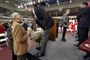 Photo - New University of Oklahoma men's basketball coach Lon Kruger speaks to fan Jerry Kershaw after a pep assembly that introduced Kruger as the new University of Oklahoma men's basketball coach on Monday, April 4, 2011, in Norman, Okla.
