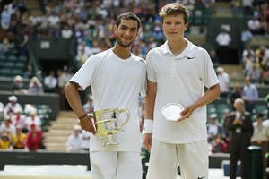 Photo - Noah Rubin of the U.S., left, holds the trophy after defeating Stefan Kozlov of the U.S., right, in the boys' singles final at the All England Lawn Tennis Championships in Wimbledon, London, Sunday July 6, 2014. (AP Photo/Alastair Grant)