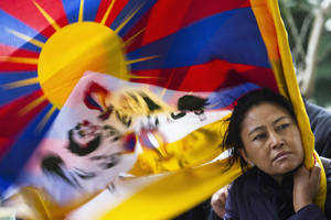photo - A Tibetan exhile holds a Tibetan flag in Dharmsala, India, as they mark the anniversary of a failed 1959 uprising against Chinese rule, Sunday, March 10, 2013. Police in India prevented a Tibetan man from setting himself on fire as hundreds of Tibetan exiles gathered to mark the anniversary in Dharmsala, the home of Tibet's government in exile. (AP Photo/ Ashwini Bhatia)