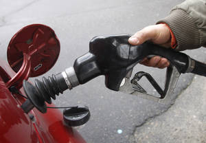 Photo - A customer puts gas into his vehicle. There are many ways to improve your gas mileage and help your vehicle run more efficiently, and there are many suggestions that simply are not true. (AP Photo)