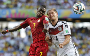 Photo - Ghana's Christian Atsu, left, battles for the ball with Germany's Benedikt Hoewedes during the group G World Cup soccer match at the Arena Castelao in Fortaleza, Brazil, Saturday, June 21, 2014. (AP Photo/Frank Augstein)