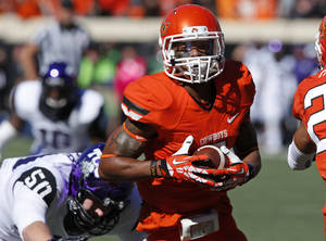 Photo - Oklahoma State's Josh Stewart (5) returns a punt for a touchdown in front of TCU defender James Power (50) in the first quarter of an NCAA college football game in Stillwater, Okla., Saturday, Oct. 19, 2013. (AP Photo/Sue Ogrocki)
