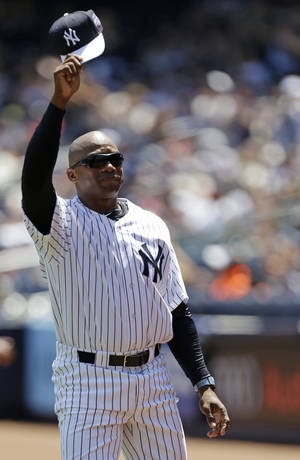 "Photo - FILE - In this June 23, 2013 file photo, former New York Yankees pitcher Orlando ""El Duque"" Hernandez tips his cap to the crowd as he is introduced before the Yankees 67th Old Timers Day baseball game  in New York. Hernandez has re-joined the New York Yankees as a minor league spring training pitching instructor. The Cuban right-hander said Tuesday, March 4, 2014,  he will be at the team's minor league complex for the next few weeks. (AP Photo/Kathy Willens, File)"