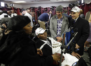 Photo - In this Sunday, Jan. 20, 2013 photo, former Baltimore Ravens NFL player O.J. Brigance, center, his wife Chanda, left, and former Olympic swimmer Michael Phelps, second from right, visit the Ravens locker room after the NFL football AFC Championship football game against the New England Patriots in Foxborough, Mass. Confined to a wheelchair as he battles Amyotrophic Lateral Sclerosis, the former Baltimore linebacker presented the Lamar Hunt trophy to the team after it beat the New England Patriots 28-13.  (AP Photo/Elise Amendola)