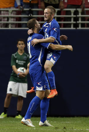 Photo - Bosnia's Edin Dzeko, left, is congratulated by teammate Edin Visca after scoring during the first half in an international friendly soccer match against Ivory Coast on Friday, May 30, 2014, in St. Louis. (AP Photo/Jeff Roberson)
