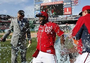 Photo - Washington Nationals' Denard Span, center, is doused by relief pitcher Tyler Clippard, right, with MASN broadcast reporter Dan Kolko, left, nearby after a baseball game against the St. Louis Cardinals at Nationals Park, Sunday, April 20, 2014, in Washington. Span hit a game-winning sacrifice fly for the Nationals' 3-2 victory. (AP Photo/Alex Brandon)