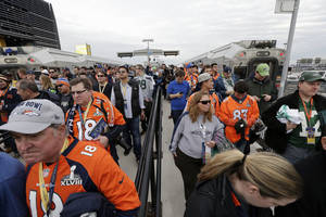 Photo - Fans arrive at Meadowlands Rail Station before the NFL Super Bowl XLVIII football game between the Seattle Seahawks and the Denver Broncos on Sunday, Feb. 2, 2014, in East Rutherford, N.J. (AP Photo/Gregory Bull)