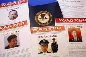 Photo - FILE - This May 19, 2014 file photo shows press material displayed at the Justice Department in Washington before a press conference by U.S. Attorney General Eric Holder to announce charges of economic espionage and trade secret theft against five Chinese military officers, all hackers in an international cyber-espionage case. In the two weeks since the Obama administration accused them of hacking into American companies to steal trade secrets, the Chinese officers have yet to be placed on Interpol's public listing of international fugitives, and there is no evidence that China would even entertain a formal request by the U.S. to extradite them. (AP Photo/Charles Dharapak, File)