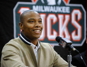 Photo - Milwaukee Bucks' Caron Butler smiles as he takes his seat during a news conference with the NBA basketball team, held before students in the Park High School gymnasium on Thursday, Sept. 5, 2013, in Racine, Wis. Butler is from Racine and is a Park High School alumnus. (AP Photo/The Journal Times, Scott Anderson)