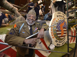 photo - Korean War veteran James McEachin, 82,  poses in front of the Rose Parade float Freedom Is Not Free by the Korean War Commemoration Committee, Saturday, Dec. 29, 2012, in Pasadena, Calif. McEachin is scheduled to ride the float in the Rose Parade on Tuesday, Jan. 1, 2013. (AP Photo/Mark J. Terrill)