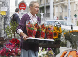 Photo - In this Sept. 5, 2013 photo, a florist carries flowers in trendy Savior Square in Warsaw, Poland. It has become one of the capital city's trendiest places after political and economic reform and attracts tourists, students and professionals with its numerous cafes and leisurely ambiance.  (AP Photo/Czarek Sokolowski)