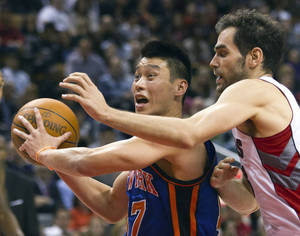 Photo - New York Knicks guard Jeremy Lin (17) drives past Toronto Raptors guard Jose Calderon during the second half of an NBA basketball game in Toronto on Tuesday, Feb. 14, 2012. (AP Photo/The Canadian Press, Frank Gunn) ORG XMIT: FNG117