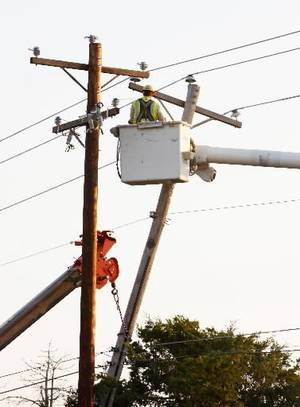 photo - Oklahoma Gas and Electric crews work to replace power lines and poles downed in an early morning wreck in Midwest City Thursday, Sept. 20, 2012. Photo by Paul B. Southerland
