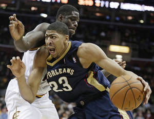 Photo - New Orleans Pelicans' Anthony Davis (23) drives past Cleveland Cavaliers' Anthony Bennett (15) during the fourth quarter of an NBA basketball game, Tuesday, Jan. 28, 2014, in Cleveland. New Orleans defeated Cleveland 100-89. (AP Photo/Tony Dejak)