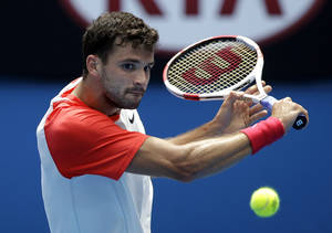 Photo - Grigor Dimitrov of Bulgaria hits a backhand return to Roberto Bautista Agut of Spain during their fourth round match at the Australian Open tennis championship in Melbourne, Australia, Monday, Jan. 20, 2014.(AP Photo/Aijaz Rahi)
