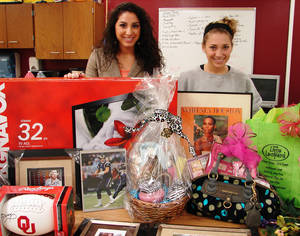 Photo - Kelsey Abraham, left, and Rylee Flowers stand with some of the items collected for the silent auction for Putnam City North High School's Heisman Week. A silent auction on Friday will be the first of many events Putnam City North High School students are staging to help Allie, 4, and Dylan, 14, who have life-threatening illnesses. Photo provided