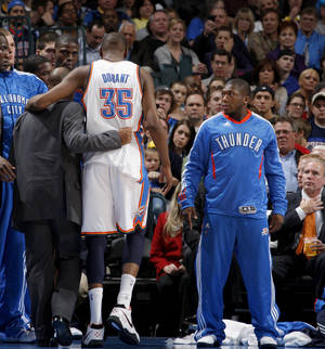 Photo - Oklahoma City's Kevin Durant (35) is helped of the court as Oklahoma City's Nate Robinson (3) and the crowd watches during the NBA basketball game between the Oklahoma City Thunder and the Indiana Pacers at the Oklahoma City Arena, Wednesday, March 2, 2011. Photo by Bryan Terry, The Oklahoman