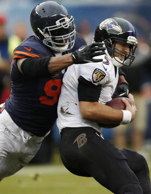 Photo - Chicago Bears defensive end Julius Peppers (90) sacks Baltimore Ravens quarterback Joe Flacco (5) during the first half of an NFL football game, Sunday, Nov. 17, 2013, in Chicago. (AP Photo/Charles Rex Arbogast)