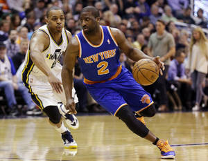 Photo - New York Knicks' Raymond Felton (2) drives around Utah Jazz's Randy Foye (8) in the first quarter during an NBA basketball game, Monday, March 18, 2013, in Salt Lake City. (AP Photo/Rick Bowmer)