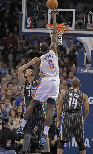 photo - Oklahoma City Thunder's Kendrick Perkins Scores over Orlando Magic's Ryan Anderson (33) in the first half as the Oklahoma City Thunder play the Orlando Magic in NBA basketball at the Chesapeake Energy Arena on Sunday, Dec. 25, 2011, in Oklahoma City, Okla.  Photo by Steve Sisney, The Oklahoman