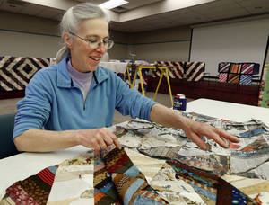 Photo - Below: Teresa Tittle, with the Norman Area Quilters Guild, separates sections of a string quilt during a quilting demonstration Saturday at the Norman Public Library.