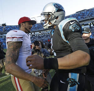 Photo - San Francisco 49ers quarterback Colin Kaepernick, left, greets Carolina Panthers quarterback Cam Newton after the second half of a divisional playoff NFL football game, Sunday, Jan. 12, 2014, in Charlotte, N.C. The San Francisco 49ers won 23-10. (AP Photo/Gerry Broome)