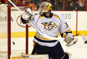Photo - Nashville Predators goalie Carter Hutton looks over his shoulder as the shot by Philadelphia Flyers' Andrej Meszaros goes in the net to tie the game with 3.6 seconds remaining, in the second period of an NHL hockey game, Thursday, Jan. 16,  2014, in Philadelphia. (AP Photo/Tom Mihalek)