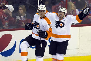 Photo - Philadelphia Flyers center Vincent Lecavalier, left, celebrates his game-winning goal with teammate Kimmo Timonen during the overtime period of an NHL hockey game against the Washington Capitals, Sunday, March 2, 2014, in Washington. The Flyers defeated the Capitals 5-4. (AP Photo/ Evan Vucci)