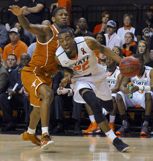 Photo - Oklahoma State guard Markel Brown, right, drives past Texas guard Julien Lewis during the second half of an NCAA college basketball game in Stillwater, Okla., Saturday, March 2, 2013. Brown scored 18 points as Oklahoma State won 78-65. (AP Photo/Brody Schmidt)