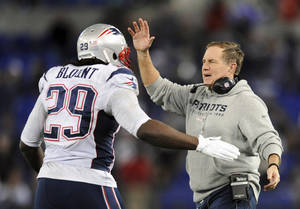 Photo - New England Patriots head coach Bill Belichick, right, celebrates with running back LeGarrette Blount after Blount scored a touchdown in the second half of an NFL football game against the Baltimore Ravens, Sunday, Dec. 22, 2013, in Baltimore. (AP Photo/Gail Burton)