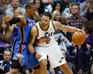 Photo - Utah Jazz guard Deron Williams (8) drives along the baseline against Oklahoma City Thunder guard Russell Westbrook (0) during the first half of their NBA basketball game in Salt Lake City, Saturday, Feb. 5, 2011. (AP Photo/Steve C. Wilson)