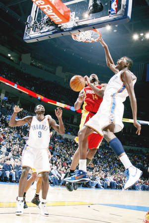Photo - Oklahoma City's Kevin Durant, right, dunks the ball over Houston's Carl Landry during action Sunday at the Ford Center.  Photo by  Sarah Phipps,  The Oklahoman