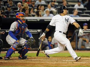 Photo - New York Mets catcher Travis d'Arnaud, left, watches New York Yankees' Yangervis Solarte hit an RBI single off of New York Mets starting pitcher Bartolo Colon in the sixth inning of an interleague baseball game at Yankee Stadium on Monday, May 12, 2014, in New York. (AP Photo/Kathy Kmonicek)