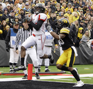 Photo - FILE -  In this Oct. 3, 2009, file photo, Arkansas State's Brandon Thompkins, left, catches a touchdown pass over Iowa's William Lowe during the second quarter of an NCAA college football game in Iowa City, Iowa.  Lowe, one of 13 Iowa football players hospitalized after a high-intensity workout in 2011, filed a lawsuit Monday, March 10, 2014, against the university claiming the university's negligence caused him physical and mental harm. (AP Photo/Charlie Neibergall, File)