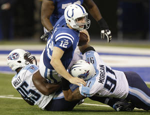 Photo - Indianapolis Colts' Andrew Luck (12) is sacked by Tennessee Titans' Kamerion Wimbley (95) and Derrick Morgan (91) during the first half of an NFL football game on Sunday, Dec. 1, 2013, in Indianapolis. (AP Photo/Michael Conroy)