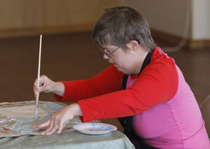 photo - Holly Welte paints during an arts and crafts class at Wings, a special needs adult community in  Edmond.