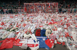 Photo -   FILE - Liverpool soccer fans arrive at Anfield Stadium to pay their respects as flower tributes cover the 'Kop' end of the field, in Liverpool, on April 17, 1989, following April 15, when fans surged forward during the FA Cup semi-final between Liverpool and Nottingham Forest at Hillsborough Stadium in Sheffield, when the crash barriers gave way, killing 96 Liverpool fans and injuring over 200 others. After a long campaign by relatives of the 96 soccer fans who were crushed to death in Britain's worst sporting disaster, some 400,000 pages of previously undisclosed papers will be released Wednesday Sept. 12, 2012, and the previously secret documents may clarify what caused the disaster and how mistakes by British authorities may have contributed to the 1989 tragedy. (AP Photo, File)