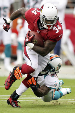 Photo -   Arizona Cardinals running back Ryan Williams (34) breaks the tackle of Miami Dolphins center Mike Pouncey, right, during the first half of an NFL football game, Sunday, Sept. 30, 2012, in Glendale, Ariz. (AP Photo/Paul Connors)