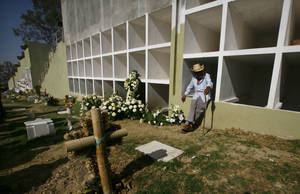Photo - A relative leans on a burial chamber during the graveside ceremony for Eva Melchor, a victim of the Mexico oil company office building explosion, in Mexico City, Saturday, Feb. 2, 2013. Melchor died Thursday, in a blast that collapsed the lower floors of Petroleos Mexicanos, or Pemex, headquarters, crushing at least 33 people beneath tons of rubble and injuring 121. (AP Photo/Marco Ugarte)