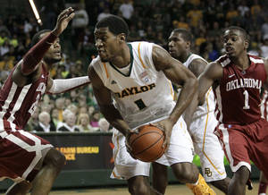 photo - Baylor 's Perry Jones III (1) drives through Oklahoma defenders Romero Osby, left, and Sam Grooms (1) for a shot attempt in the second half of an NCAA college basketball game Saturday, Feb. 25, 2012, in Waco, Texas. Baylor defeated Oklahoma 70-60. (AP Photo/Tony Gutierrez) ORG XMIT: TXTG211