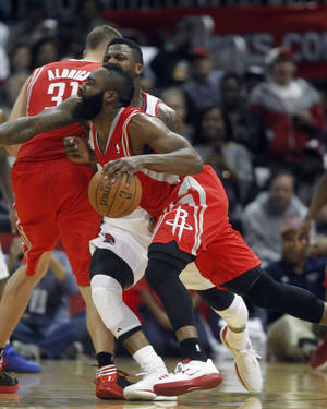 photo -   Houston Rockets shooting guard James Harden, foreground, drives against Atlanta Hawks point guard Devin Harris (34) in the first half of an NBA basketball game Friday, Nov. 2, 2012 in Atlanta. (AP Photo/John Bazemore)