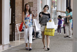 photo - Shoppers walk through the South Shore Mall in Braintree, Mass., this week.  AP Photo
