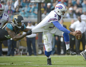 Photo - Jacksonville Jaguars defensive end Andre Branch (90) grabs Buffalo Bills quarterback EJ Manuel (3) by the jersey to stop him during the first half of an NFL football game in Jacksonville, Fla., Sunday, Dec. 15, 2013.(AP Photo/Phelan M. Ebenhack)