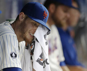 Photo - New York Mets starting pitcher Zack Wheeler wipes his face with a towel while sitting in the dugout after allowing six runs on six hits in two innings of an interleague baseball game against the Oakland Athletics in New York, Wednesday, June 25, 2014. The Athletics defeated the Mets 8-5. (AP Photo/Kathy Willens)