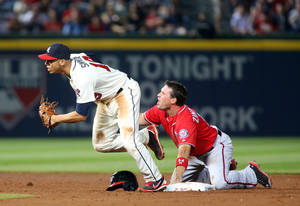 Photo - Washington Nationals' Ryan Zimmerman, right, reacts after being tagged out by Atlanta Braves shortstop Andrelton Simmons, left, at second base on a pickoff by Braves starting pitcher Alex Wood in the fifth inning of a baseball game on Saturday, April 12, 2014, in Atlanta. (AP Photo/Jason Getz)