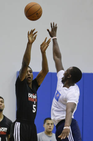 Photo - Detroit Pistons' Kartavious Caldwell-Pope (5) shoots a 3-point shot over Oklahoma City Thunder's Reggie Jackson, right,  during an NBA summer league basketball game, Tuesday, July 9, 2013, in Orlando, Fla. (AP Photo/John Raoux) ORG XMIT: DOA115