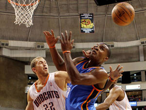 Photo - Thunder guard Elijah Millsap (8), right,  battles Bobcats forward Matt Rogers (22) for a loose ball. AP photo
